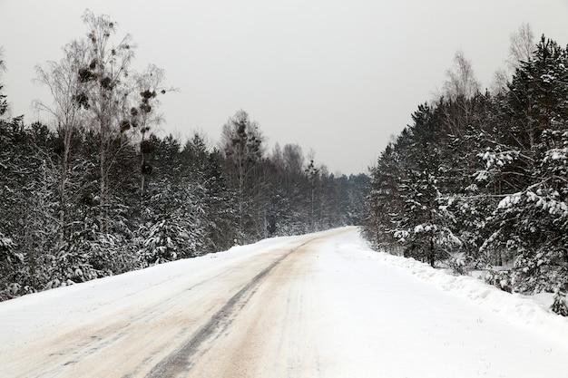 Met sneeuw bedekte weg in het winterseizoen. close-up foto