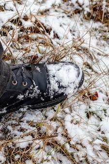 Met sneeuw bedekte zwarte laars van een man op zijn voeten tijdens een wandeling in een winterpark, bovenaanzicht. man in zwarte laarzen in de sneeuw