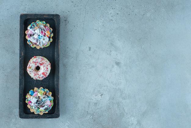 Met snoep bedekte cupcakes en donuts op een zwart dienblad op marmeren oppervlak