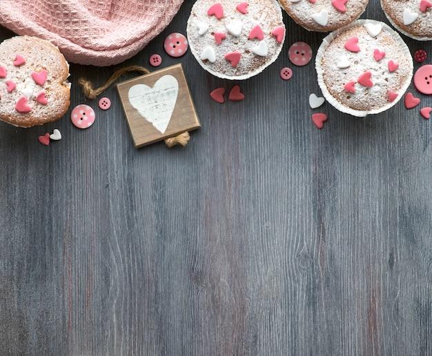 Met suiker bestrooide muffins met roze en witte fondant glazuur harten,