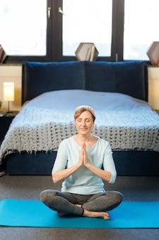 Met vastgebonden haar. rustige volwassen vrouw in comfortabele kleding die yoga doet in haar stijlvolle appartement met verbonden hand voor haar