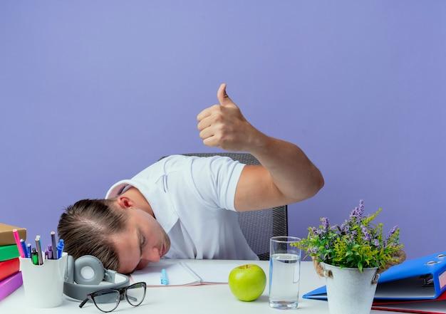 Met verlaagd hoofd jonge knappe mannelijke student zittend aan een bureau met schoolhulpmiddelen zijn duim omhoog geïsoleerd op blauwe achtergrond