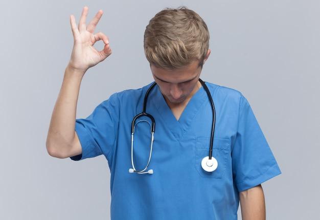 Met verlaagd hoofd jonge mannelijke arts die artsen eenvormig met stethoscoop draagt die ok gebaar toont dat op witte muur wordt geïsoleerd