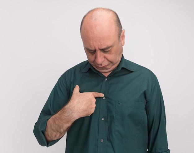 Met verlaagd hoofd man van middelbare leeftijd dragen groene t-shirt zetten vinger zelf geïsoleerd op een witte muur