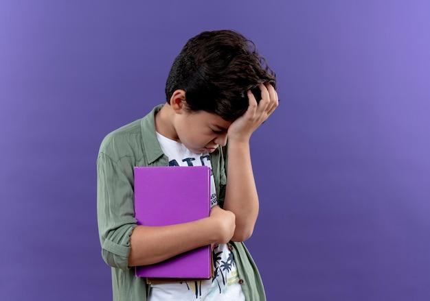 Met verlaagd hoofd triest klein schooljongen boek houden en hand op het hoofd zetten geïsoleerd op paarse muur met kopie ruimte