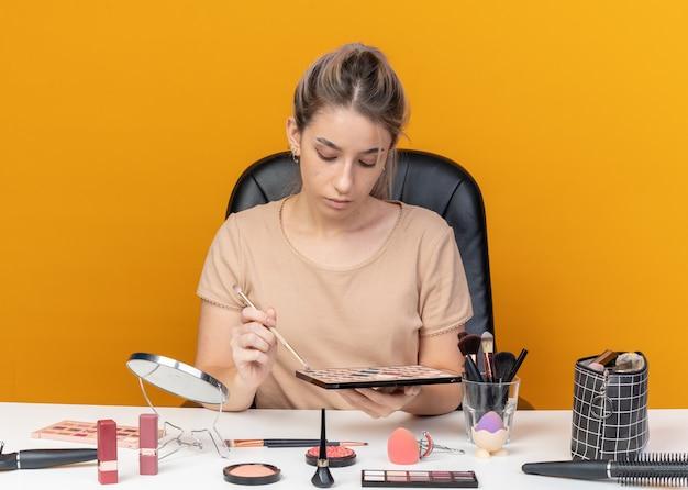Met verlaagd hoofd zit jong mooi meisje aan tafel met make-up tools oogschaduw toe te passen met make-up borstel geïsoleerd op oranje achtergrond