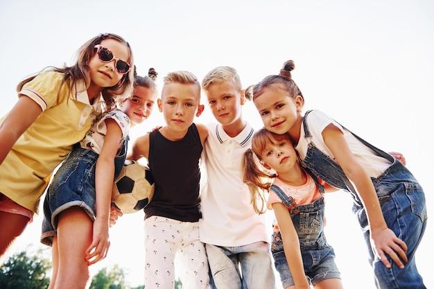 Met voetbal. portret van kinderen die samen staan en poseren voor de camera.