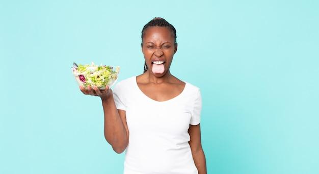 Met vrolijke en rebelse houding, grappen makend en tong uitsteken en een salade vasthouden