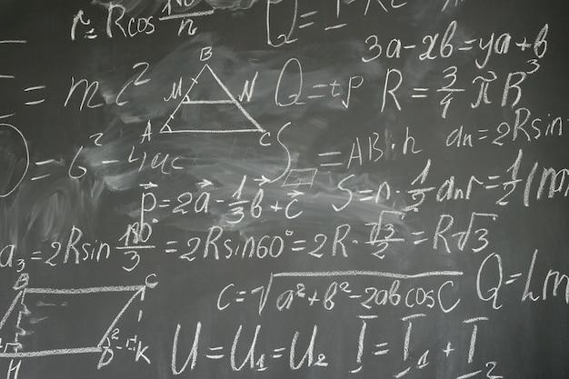 Met wiskundige formules geschreven in wit krijt op een zwarte bordachtergrond