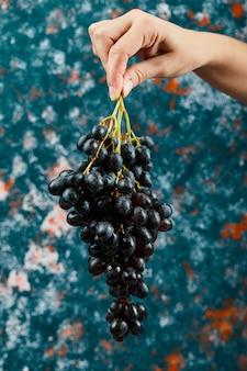 Met zwarte druiven op blauwe achtergrond. hoge kwaliteit foto