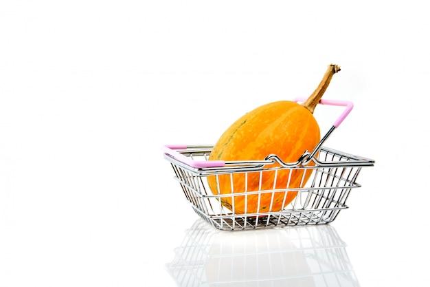 Metaal het winkelen mand met een pompoen op wit wordt geïsoleerd dat.