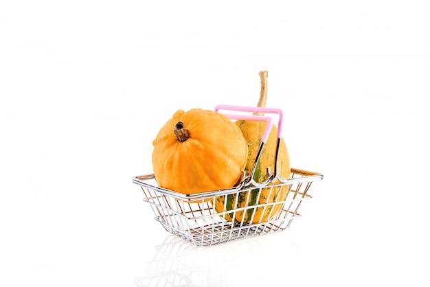 Metaal het winkelen mand met pompoenen op wit worden geïsoleerd dat.
