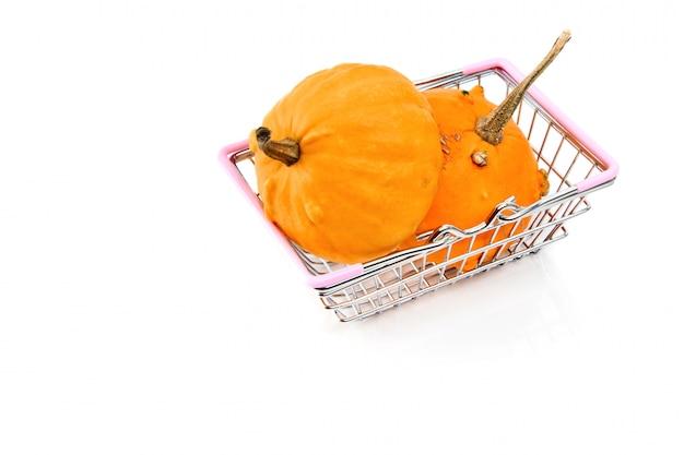 Metaal het winkelen mand met twee pompoenen die op wit worden geïsoleerd.