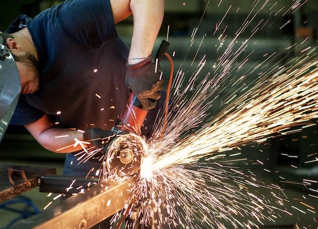 Metaalarbeider die een staalstaaf snijdt