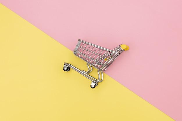 Metaalboodschappenwagentje op roze en gele achtergronden.