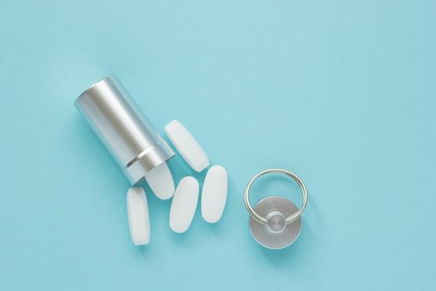 Metaalcontainer en pillen op een blauwe achtergrond, close-up