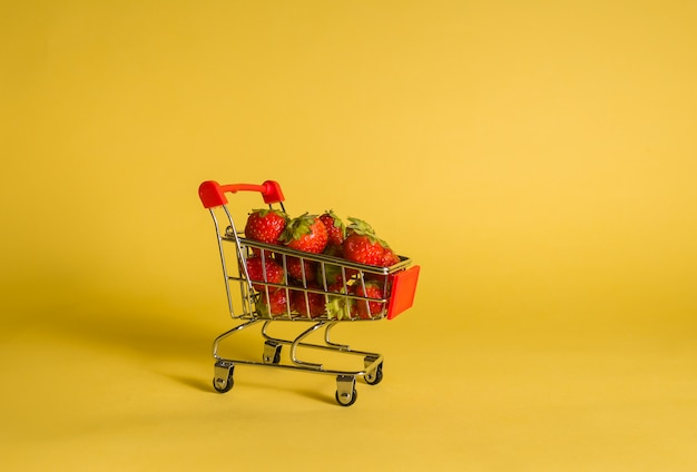 Metaalkar met aardbeien op een gele geïsoleerde ruimte