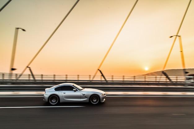 Metaalkleursportwagen op de brug in de zonsondergang.