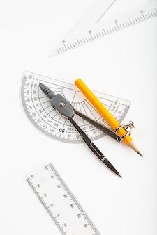 Metaalkompas een hoogste mening die op wit bureau wordt geïsoleerd