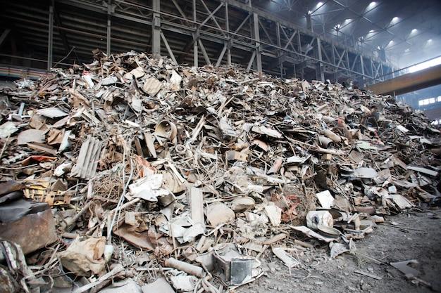 Metaalschroot over roestig ijzerafval op schroothoop. ijzeren grondstoffen klaar voor recycling.