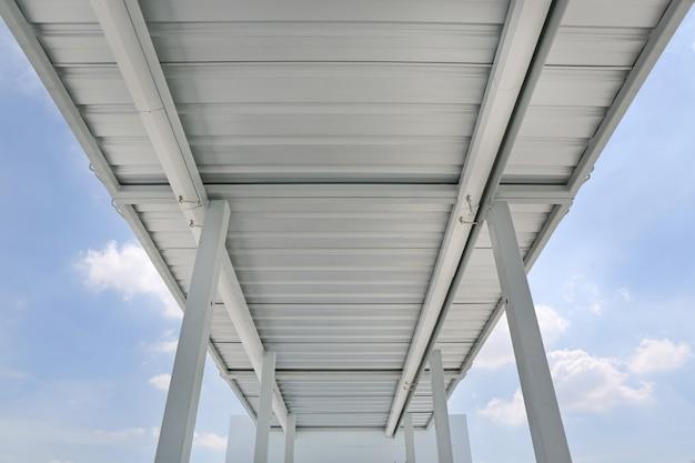 Metaalstructuur onder dak tegen wolkenhemel