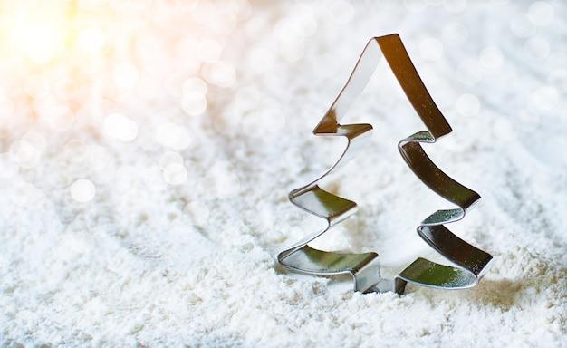 Metaalvorm voor koekjes in de vorm van sparren. vorm om het deeg tegen de achtergrond van bloem te snijden