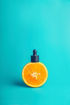 Metafoor, een fles met een serum, boter in een sinaasappel. het concept van vitamine c in cosmetica en aromatherapie.