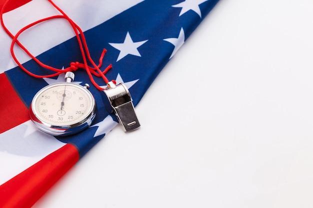 Metal sport whistle en stopwatch op amerikaanse vlag