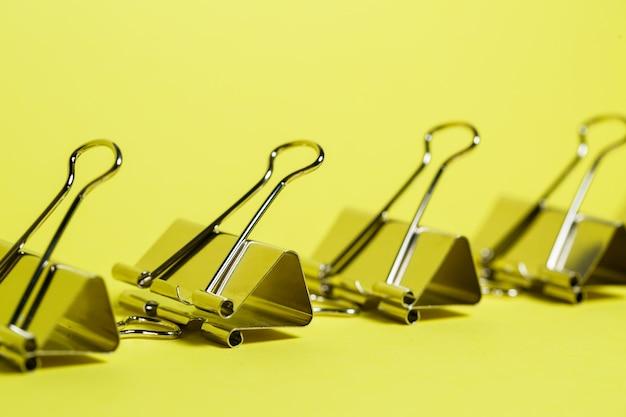Metalen bindmiddelen op een gele achtergrond. accessoires voor briefpapier. paperclip