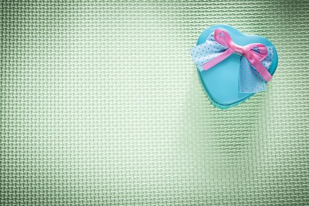 Metalen blauwe hartvormige geschenkdoos op vakantie met een groen oppervlak
