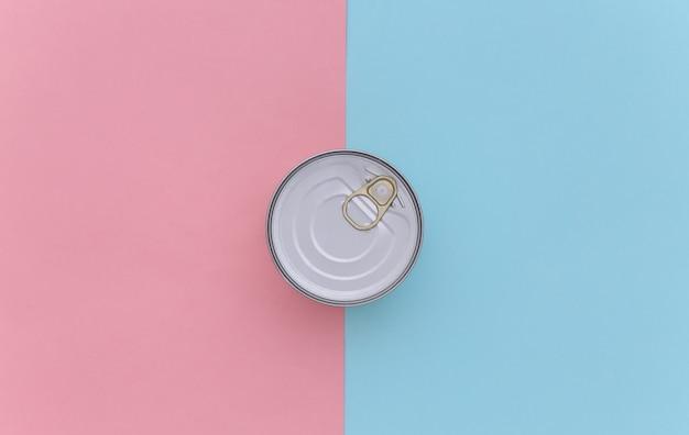 Metalen blikje ingeblikt voedsel op blauw roze achtergrond. bovenaanzicht