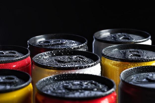 Metalen blikjes energiedrankjes op zwart met waterdruppels