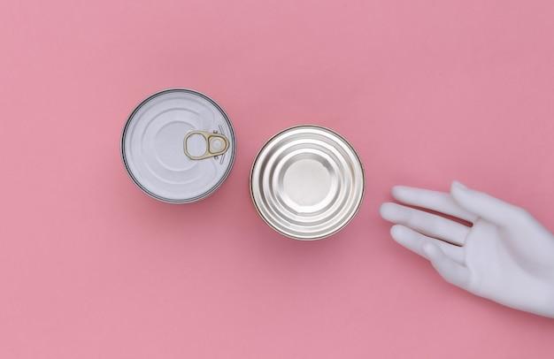 Metalen blikjes ingeblikt voedsel en mannequin hand op roze achtergrond. minimalisme. bovenaanzicht