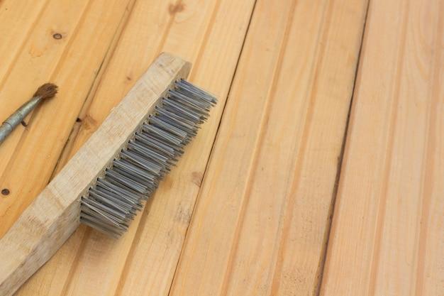 Metalen borstel voor reparatie op de houten vloer