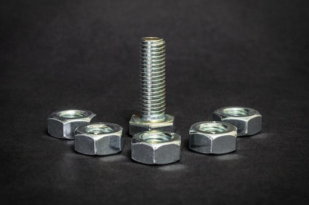 Metalen bouten en moeren op zwarte achtergrond worden gebruikt in de bouw