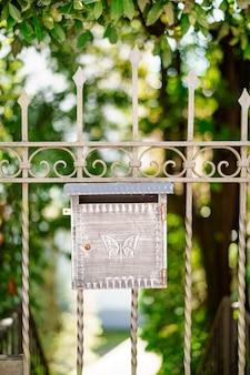 Metalen brievenbus met vlinderpatroon op de poort