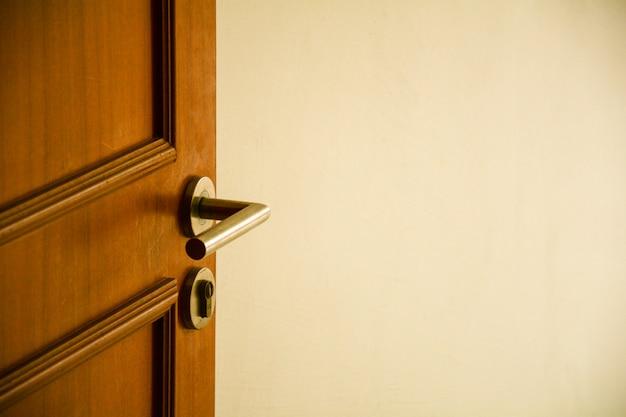 Metalen deurgrepen bij houten deur