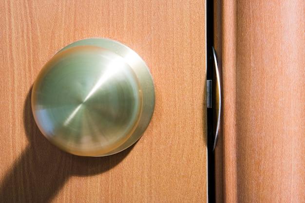 Metalen deurkruk in houtstructuur deur met schaduw