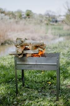 Metalen draagbare barbecue met brandend brandhout en rode vlammen