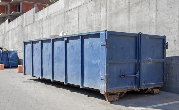 Metalen duurzame blauwe industriële vuilnisbak voor buitenafval op de bouwplaats. grote afvalmand voor huishoudelijk of industrieel afval. een stapel afval.