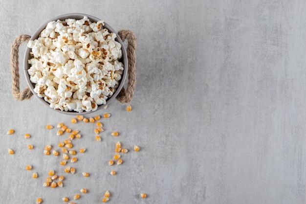 Metalen emmer gezouten popcorn geplaatst op stenen achtergrond.