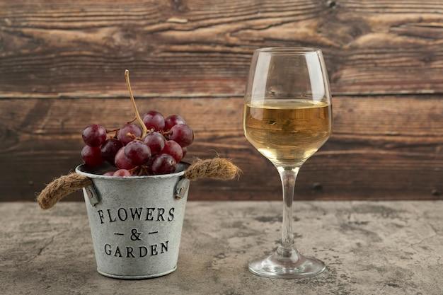 Metalen emmer met rode verse druiven en glas witte wijn op marmeren oppervlak.