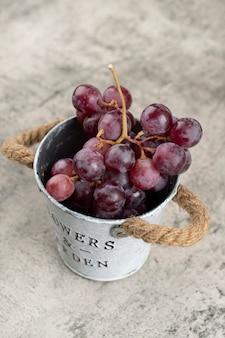 Metalen emmer met sappige rode druiven op stenen achtergrond.