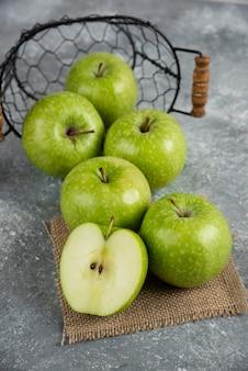 Metalen emmer met verse groene appels op marmeren tafel.