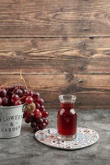 Metalen emmer rode verse druiven en glas sap op marmeren tafel.