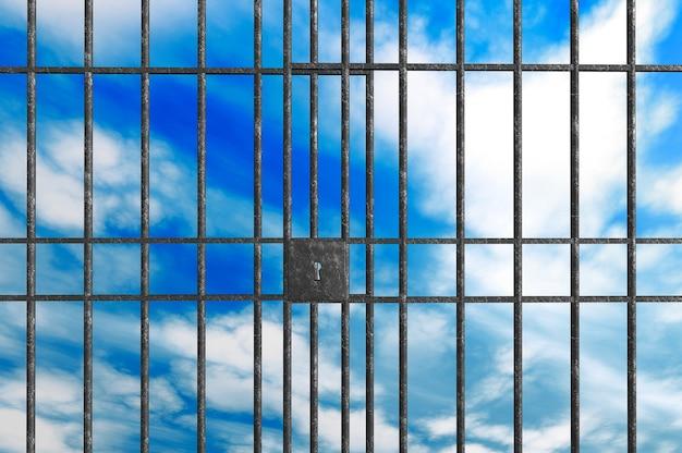 Metalen gevangenisstaven op een hemelachtergrond