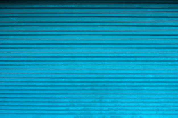 Metalen gordijn deur textuur. achtergrond van de winkel met gesloten metalen blauwe gordijnen