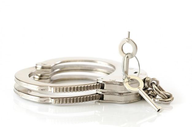 Metalen handboeien en sleutel in sleutelgat
