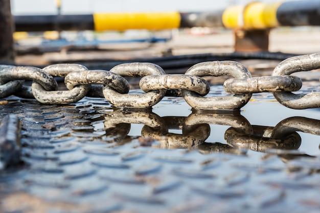 Metalen ketting met reflectie op de vloer van de plaat