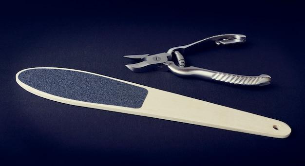Metalen kniptang voor nagels en rasp voor hakken op een donkere ruimte